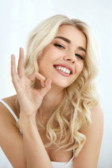 Beautiful Smiling Woman Showing Okay Sign With Hand Indoors.