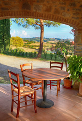 Beautiful view with table and chairs at a open terrace in italian village, Italy.