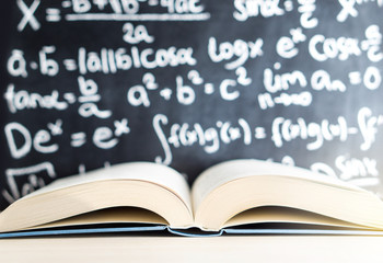 Knowledge, education, mathematics, science and wisdom concept. Open book in front of a blackboard and chalkboard full of math writing in school classroom.