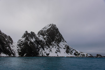 Rock with snow in sea