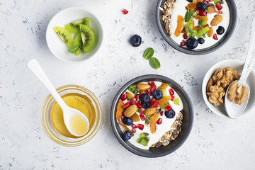 Yogurt, milk porridge, granola for breakfast with different berries, nuts and fruits: kiwi, pomegranate, dried apricots, blueberries, almonds and honey. Portionally. Top view Food concept.