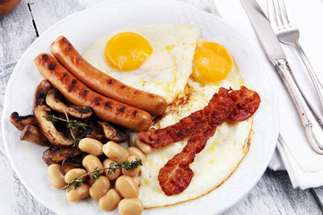 Traditional full English breakfast with fried eggs, sausages, beans, mushroomsand bacon on wooden background
