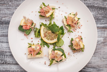 Canapes with Salmon fish and Arugula Leaves and Butter Cream. top View. White Plate on Wooden Gray Background.