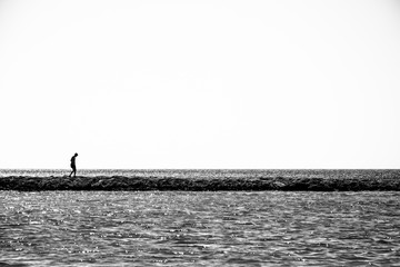 Lonely child walks on a thin coastline. Minimalistic black and white photo.