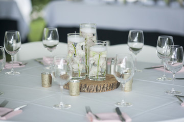 Table decorated for wedding reception with orchids in water.