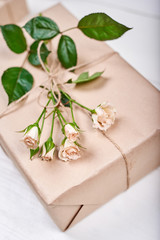 Gift box with branch of fresh roses with leaves on wooden table, copy space. Holiday background, sale, shopping. Greeting card for Valentines Day, Womens Day, Mothers Day, birthday, Easter, flat lay