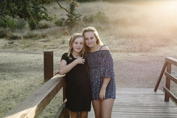 Portrait of loving sisters standing on wooden bridge