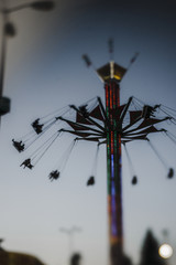 Low angle view of silhouette people enjoying in amusement park ride against clear sky during dusk