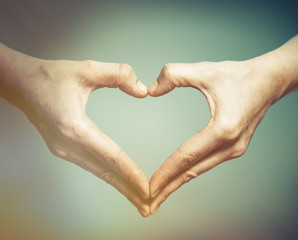 Two hands in the shape of a heart. The concept of love, harmony, caring.