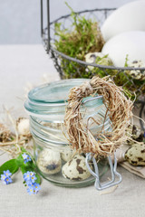 Tiny hay wreath on glass jar with quail eggs