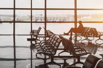 Waiting room in airport terminal departure area near gates: hall with rows of armchairs, glass facade, take-off field and airplane in the background, silhouette of passenger waiting for his flight