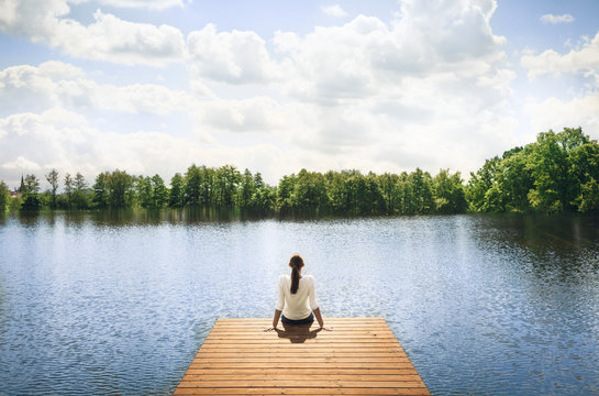 Woman relaxing on wooden dock by a beautiful lake. Peace and tranquility in nature.