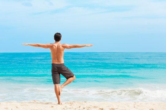 Male yoga stretch on the beach.