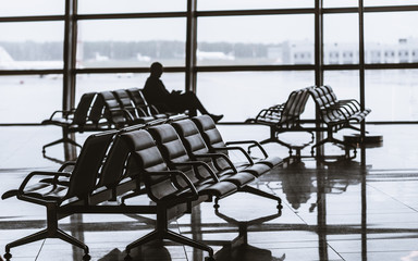 Silhouette of man sitting on armchair next to glass window of modern waiting hall in departure area of contemporary airport terminal and waiting for his flight; take-off field and airplanes behind