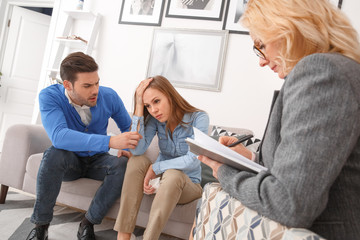 Young couple with psychologist family therapy husband trying to talk