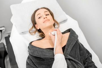 Young woman patient during the ultrasound examination of a thyroid lying on the couch in medical office