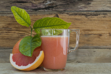 Vaso con zumo de pomelo y un trozo de la fruta