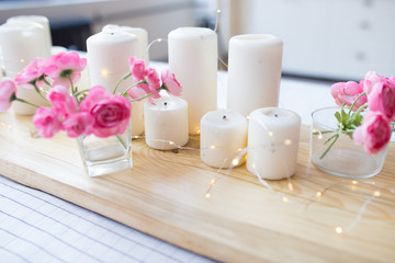 candles with lights. composition on the table. cute home decor with candles and flowers