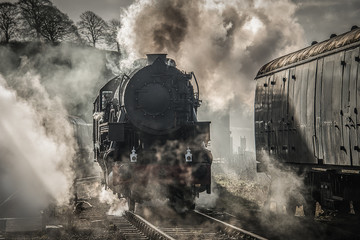 A early morning back lit photograph of a steam train smoking and letting off steam atmospheric image