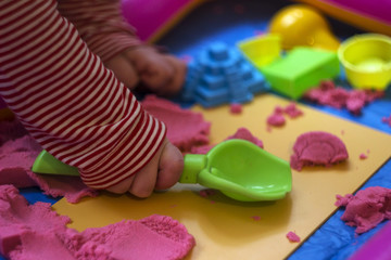 Pink kinetic sand, educational game for children. The development of motor skills in boys and girls