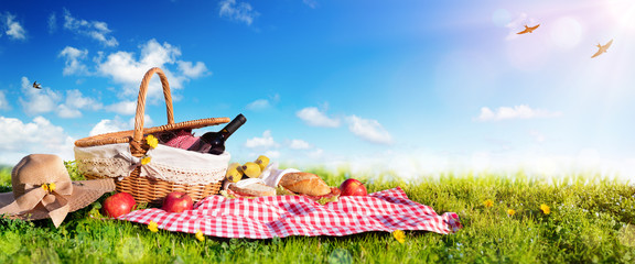 Foto op Canvas Picknick Picnic - Basket With Bread And Wine On Meadow