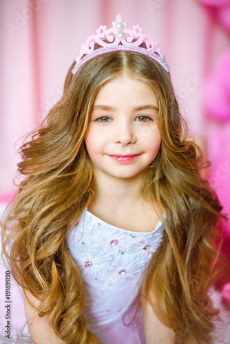 Girl With Blond Long Hair In Light Pink Dress Of A Princess And