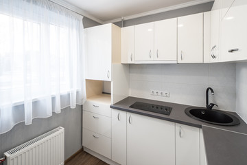 Kitchen in flat. White furniture.