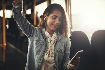 Young woman riding on a bus listening to music