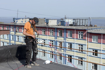 steeplejack testing his gear on the roof of the building