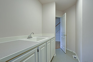 Detail view of white laundry room with shaker cabinets.
