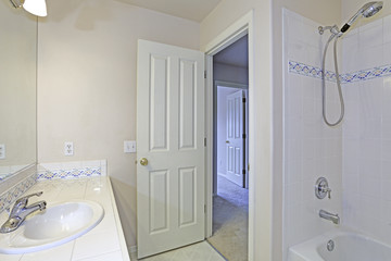 Interior of white bathroom with mosaic backspalsh tiles.