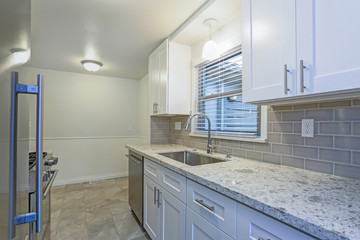 Photo of a small compact kitchen with white shaker cabinets