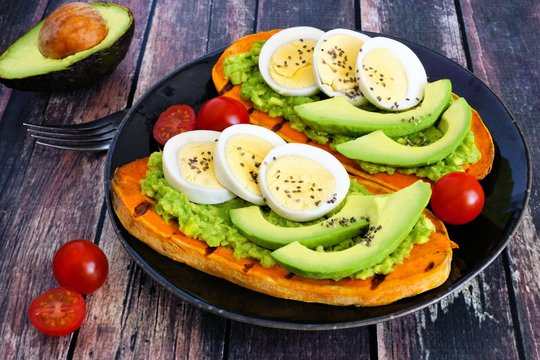 Sweet potato toasts with avocado, eggs and chia seeds on a dark plate. Table scene with a wooden background.