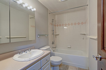 White bathroom design with vanity cabinet and tub
