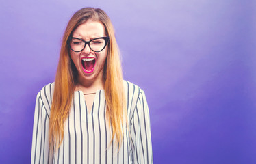 Young woman screaming on a solid background