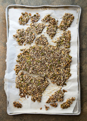 Broken seed crackers on parchment paper on a baking sheet