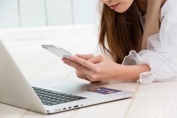 クレジットカード・スマートフォンを操作する女性