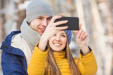Portrait of young couple in a bright clothes do a selfie in a forest in the winter