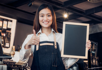 Asian female barista wear jean apron thumbs up at blank blackboard coffee menu at counter bar with smile face,cafe service concept,business owner start upLeave space for adding your text