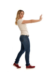 full length portrait of blonde girl wearing simple shirt and jeans, standing pose on white background.