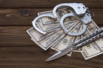 handcuffed knife and money dollars. Crime and punishment, criminal, theft. Armed attack.