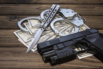 handcuffs gun knife and money dollars. Crime and punishment, criminal, theft. Armed attack.