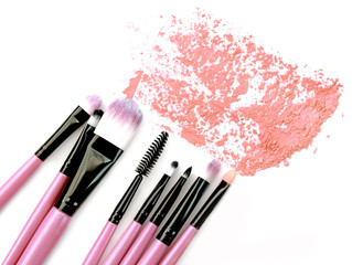 Various makeup brushes crushed powder isolated over white background