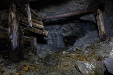 Underground abandoned gold ore mine shaft tunnel gallery with wooden timbering