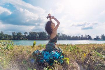 beautiful young boho woman sitting on grass outdoors