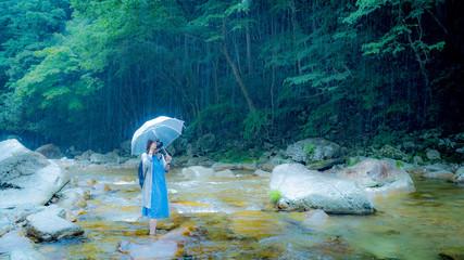 雨の川と少女