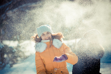 Girl in winter. A young girl is having fun in a winter park with friends. Active rest in winter. Young woman in a yellow coat against snowy background. students playing with snow