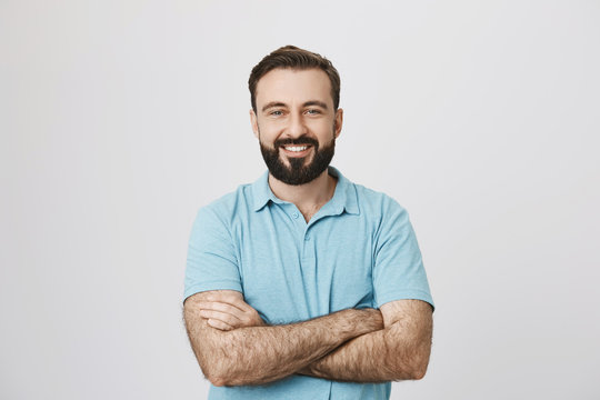Portrait of a handsome bearded man smiling looking to the camera with his hands crossed isolated on white background. This person looks like an ordinary guy who is sincere and ready to help everyone.