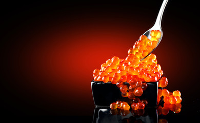 Photo sur Toile Roe Caviar in a spoon. Salmon caviar in a bowl over black background. Closeup trout caviar