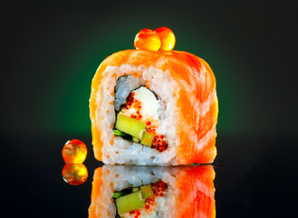 Sushi roll over black background. California sushi roll with salmon, vegetables, flying fish roe closeup. Japanese food